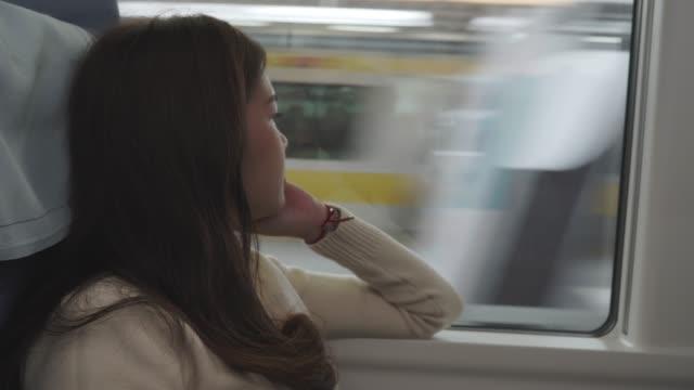 電車の窓から外を見ているアジアの女性 - 乗客点の映像素材/bロール