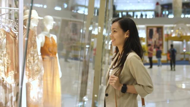 asiatische frau schaut durch das schaufenster - schaufenster stock-videos und b-roll-filmmaterial