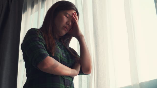 Asian woman looking through window self-quarantine for coronavirus