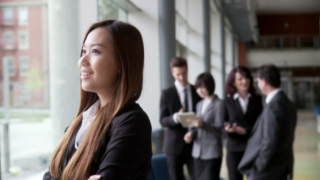 Asian Woman looks to the future Beautiful Asian woman looks with a gaze towards the future with a positive outlook towards global business opportunities, while her team mates discuss strategy in the background. representing stock videos & royalty-free footage