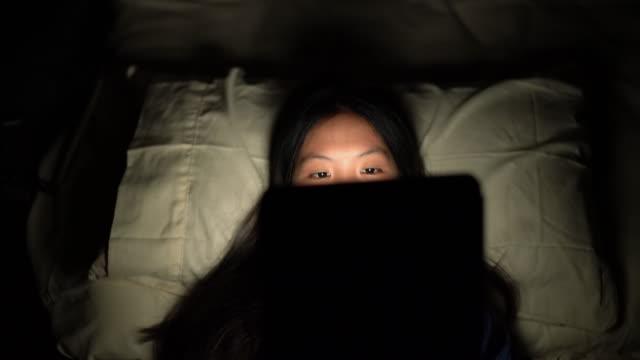 デジタルタブレットを使用して暗い寝室で背中に横たわっているアジアの女性 - スマホ ベッド点の映像素材/bロール