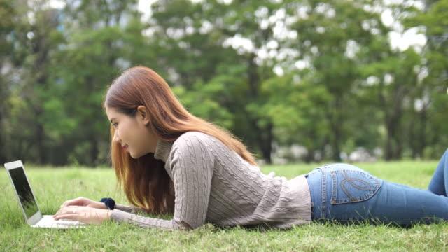 asiatisk kvinna liggande på gräset och använder bärbar dator - ligga på mage bildbanksvideor och videomaterial från bakom kulisserna
