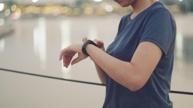 asiatisk kvinna övervaka hennes kör prestanda på smartwatch på morgonen - armbandsur bildbanksvideor och videomaterial från bakom kulisserna