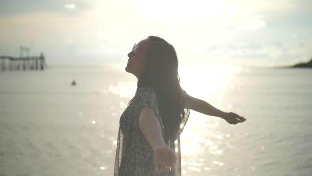 vídeos de stock e filmes b-roll de asian woman on beach with opening arms - braços no ar