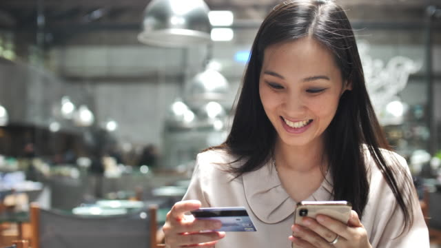 Asian Woman online Shopping on her Smart phone