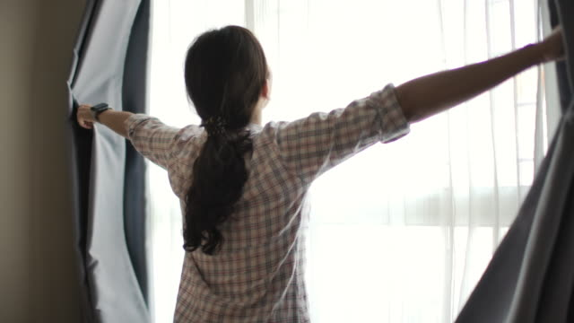 asian woman opening curtain - gente serena video stock e b–roll
