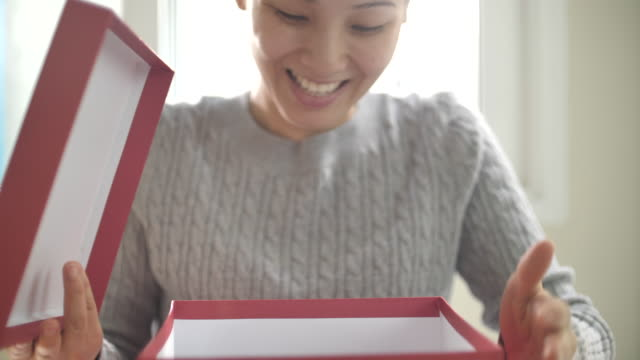 Asian woman opening gift box at home, Slow motion