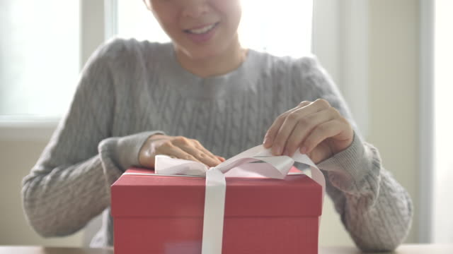 Asian Woman opening unpacking Red Gift box