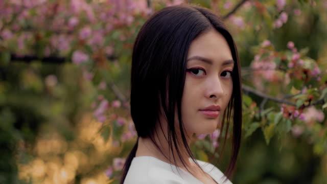アジアの女性の花の花を春に屋外 - 美人点の映像素材/bロール