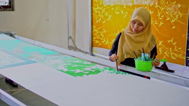asiatisk kvinna målning på en siden i batik verkstad - anständig klädsel bildbanksvideor och videomaterial från bakom kulisserna