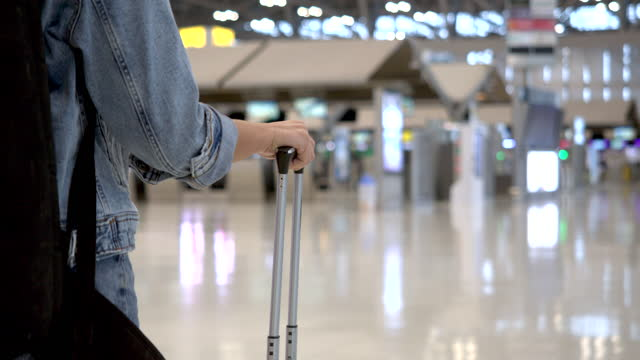 Asian woman passenger wearing blue jeans Drag the wheeled suitcase Inside the passenger building 4k video footage Asian woman passenger wearing blue jeans Drag the wheeled suitcase Inside the passenger building continuity stock videos & royalty-free footage