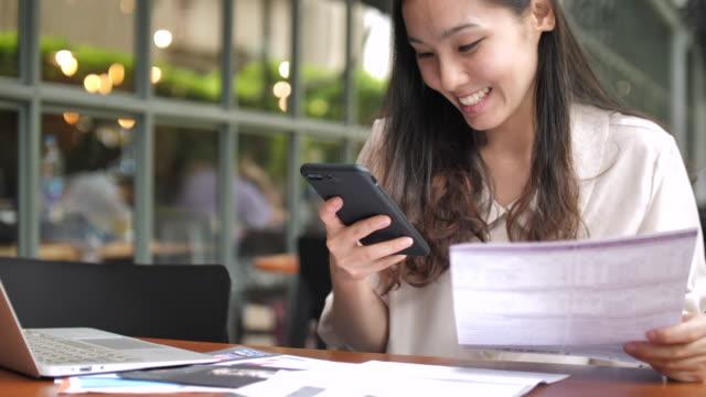 vídeos y material grabado en eventos de stock de mujer asiática pagar factura en línea - hipotecas y préstamos