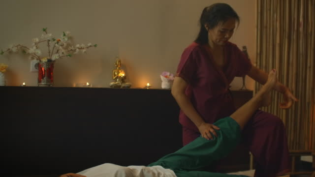 vídeos de stock e filmes b-roll de asian woman performs traditional thai massage to beautiful european woman. rehabilitation and treatment after injuries with the help of massage. relax and rest from massage of legs, arms and back. - cultura tailandesa