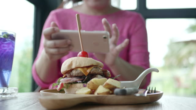 Asian woman photographing delicious burger in fastfood restaurant.