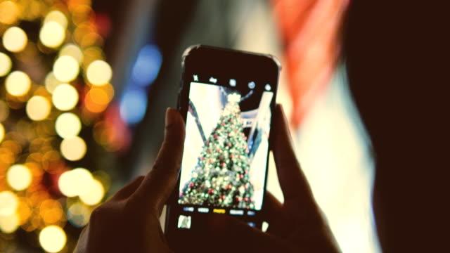 Asian woman photographs a city christmas tree
