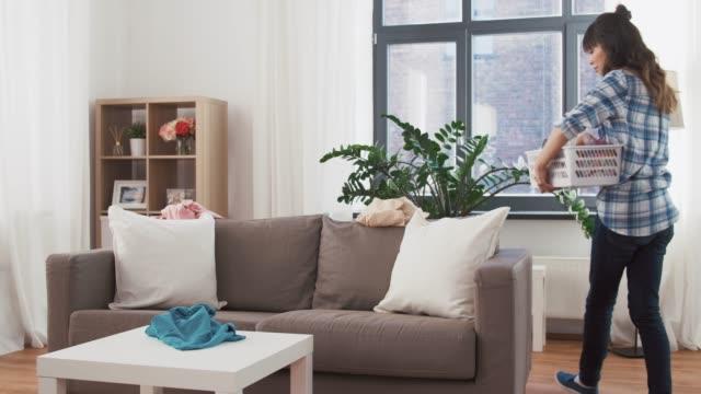 asyalı kadın evde kirli çamaşır toplama - ev temizleme stok videoları ve detay görüntü çekimi