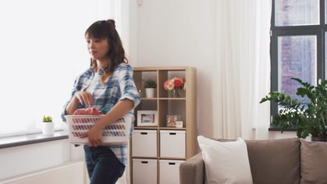 アジアの女性は自宅で汚れた洗濯を選びます - 楽しい 洗濯点の映像素材/bロール
