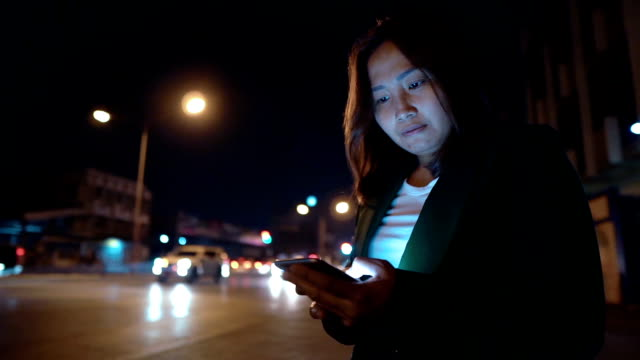 asian woman play smartphone at the night side road - lokalizacja poza usa filmów i materiałów b-roll