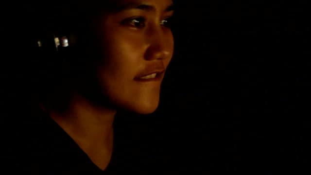 アジアの女性は、暗闇の中でコンピューター ゲームをプレイします。 - ゲーム ヘッドフォン点の映像素材/bロール