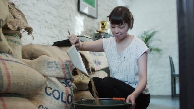 アジアの女性を注ぐコーヒー生豆 (スローモーション) - カフェ文化点の映像素材/bロール