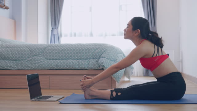 vídeos de stock, filmes e b-roll de mulher asiática praticando yoga em casa com laptop no quarto - personal trainer