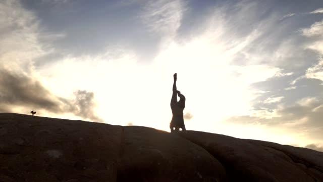 asiatisk kvinna som tränar yoga på berget . person meditera utomhus och njut av orange soluppgång . - endast en ung kvinna bildbanksvideor och videomaterial från bakom kulisserna