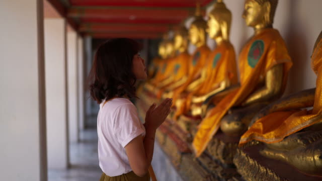 asian woman praying with buddha in temple