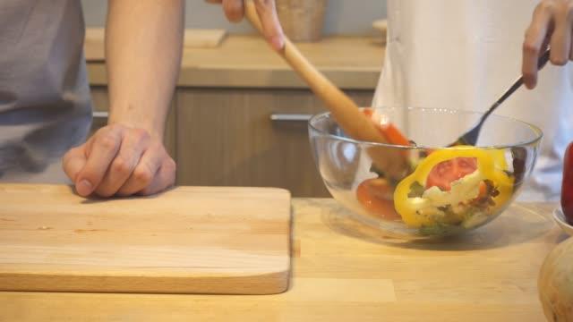 la donna asiatica prepara il cibo per insalata in cucina. bella coppia asiatica felice stanno cucinando in cucina. la giovane coppia asiatica si diverte molto mentre resta a casa. stile di vita di coppia a casa concetto. - romanticismo concetto video stock e b–roll