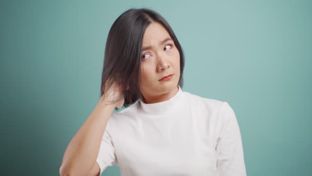 Asian woman putting a finger into her ear and standing isolated over blue background. Health care concepts. 4k video.