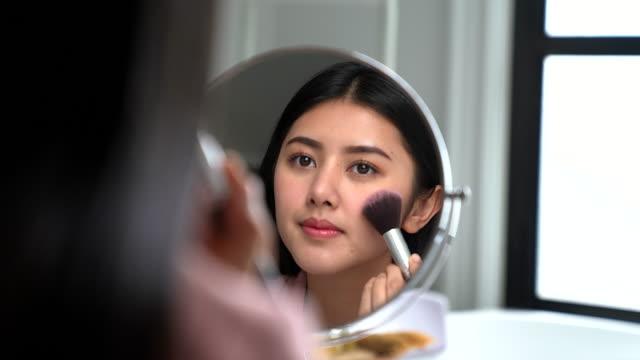 バスルームの鏡の前で彼女の化粧をしてアジアの女性 - マスカラ点の映像素材/bロール