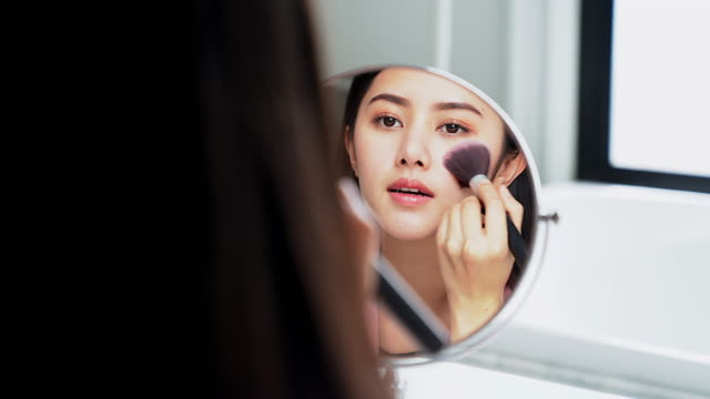 Asian woman putting on her makeup in front of the bathroom mirror Asian woman putting on her makeup in front of the bathroom mirror highlights hair stock videos & royalty-free footage