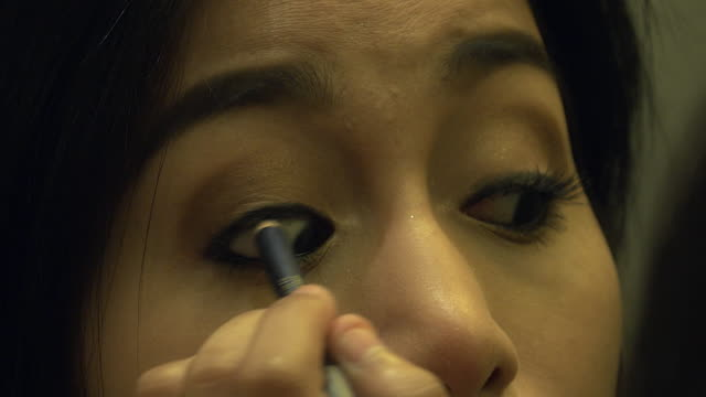 4K: Asian woman putting on her makeup in front of the bathroom mirror video