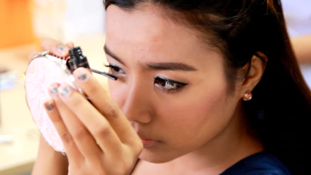 Asian Woman putting on mascara, closeup video