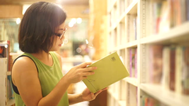 Asian woman reading a book at the bookstore against shelves backgrounds.