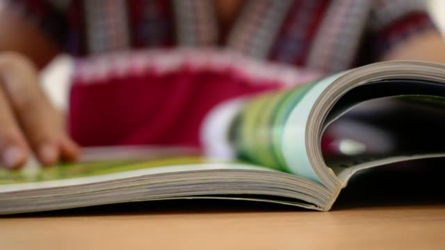 stockvideo's en b-roll-footage met aziatische vrouw die een boek in de bibliotheekruimte leest. - woman home magazine