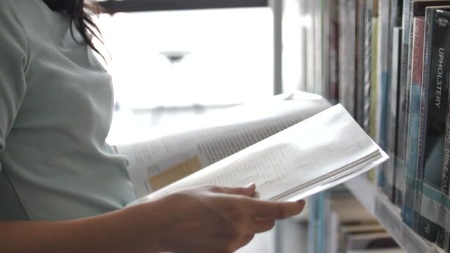 Asian Woman Reading a book on bookshelf in the library Asian Woman Reading a book on bookshelf in the library textbook stock videos & royalty-free footage