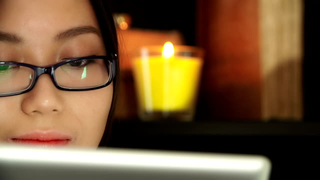 Asian woman reading a tablet video