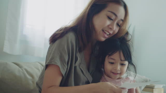 Asian Woman Reading Postcard on Mothers Day and Smiling With Her Daughter