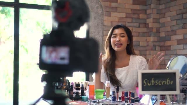 アジアの女性は三脚のデジタル一眼レフで化粧品についてのビデオを記録 - スタジオ 日本人点の映像素材/bロール