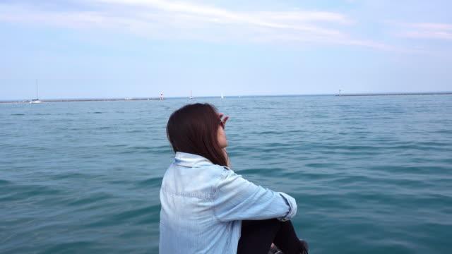 アジアの女性のリラックスした背景にミシガン湖、シカゴ、イリノイ州、アメリカ合衆国 - 米国旅行点の映像素材/bロール