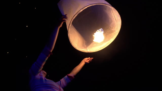 Asian Woman Releases A Sky Lantern Asian woman releases a sky lantern at a festival. lantern stock videos & royalty-free footage
