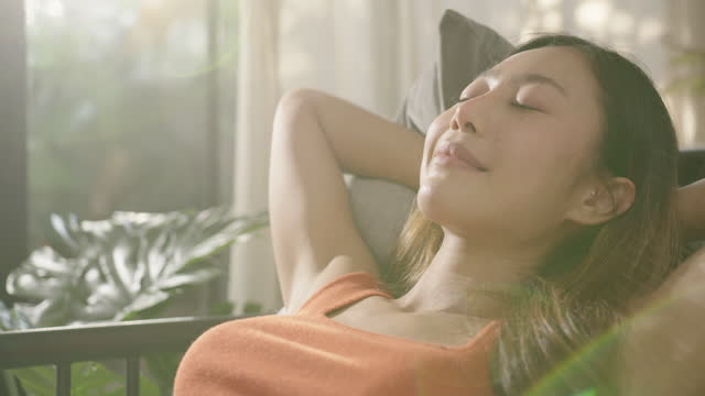 donna asiatica che riposa respira aria fresca sentendo equilibrio mentale godendosi il benessere a casa sul divano, gli occhi chiusi mettono le mani dietro la testa rilassandosi sul comodo divano in un accogliente soggiorno caldo e leggero - ritemprarsi video stock e b–roll
