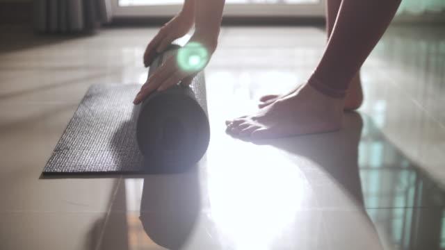 vídeos de stock e filmes b-roll de asian woman rolling yoga mat at home, slow motion - treino em casa