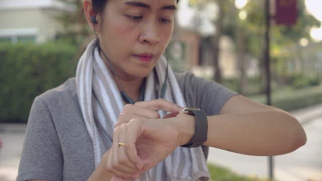 아시아 여성 러너 스마트 시계를 확인 - 검사 보기 스톡 비디오 및 b-롤 화면