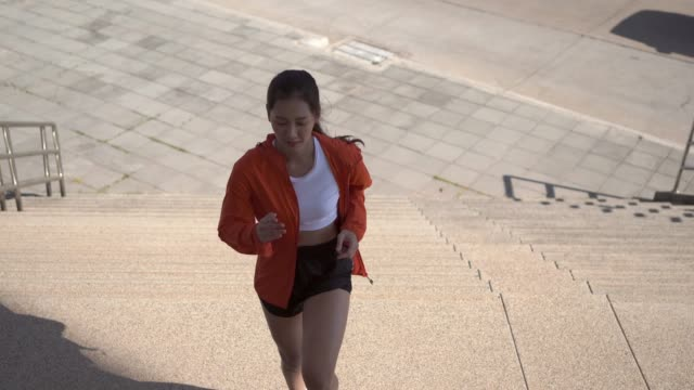 Asian woman runners she exercises in the morning up the stairs