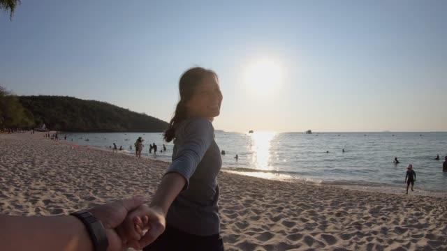 stockvideo's en b-roll-footage met aziatische vrouw loopt met vriendje naar het strand slow motion - twilight