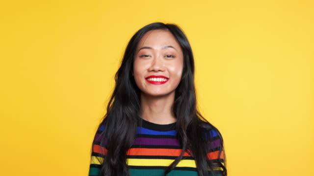 asiatisk kvinna säger ja och sedan säga nej på gul bakgrund - huvud bildbanksvideor och videomaterial från bakom kulisserna