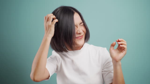 Asian woman  scratching her head and standing isolated over blue background. Health care concepts. 4k video. video