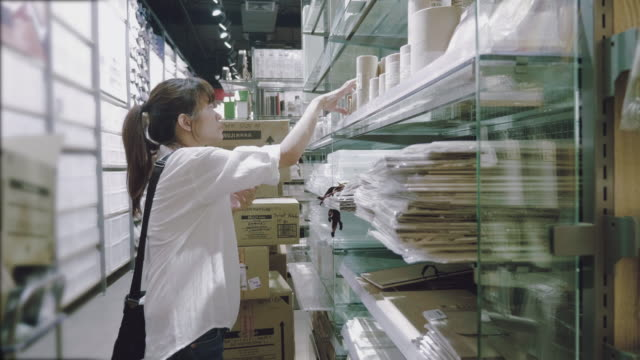 Asian woman searching for a book in a bookstore video