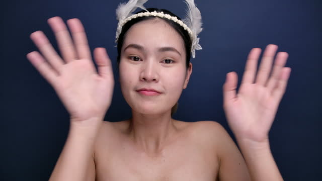 4K Asian woman, she is happy and sexy, blue studio backdrop
